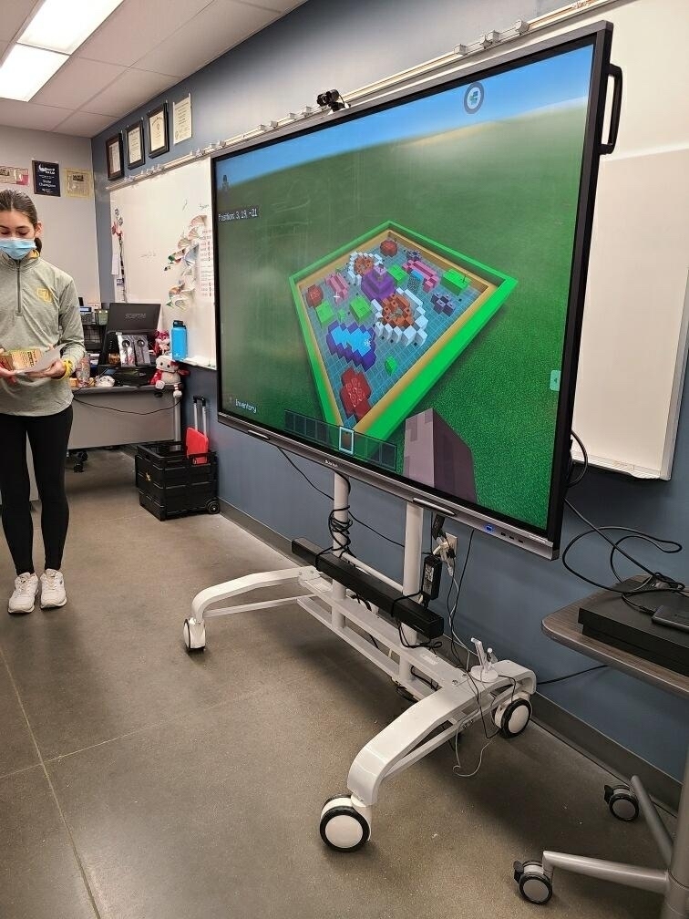 Student standing with a TV