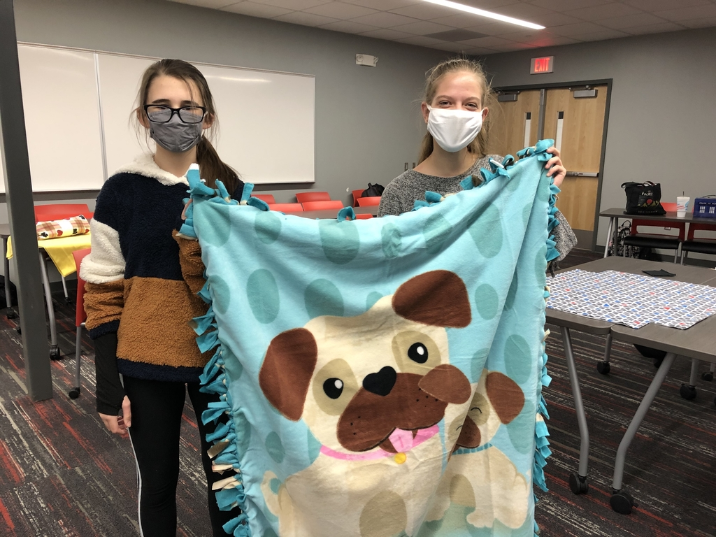 Students showing a blanket they made