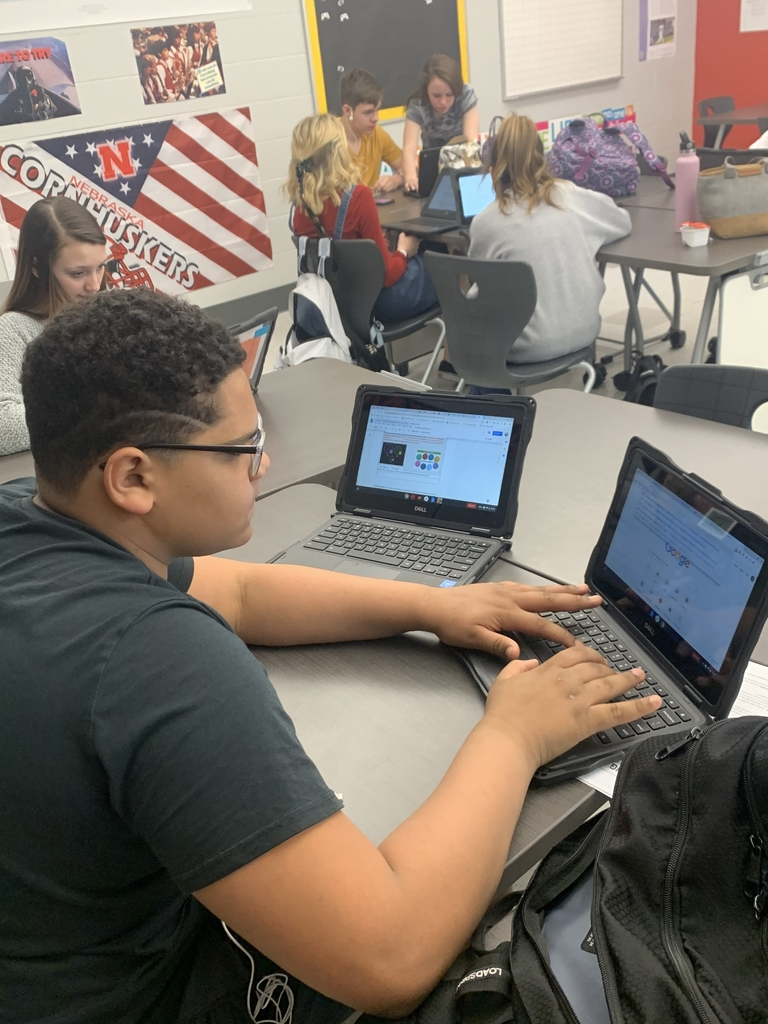 Student working on Chromebook while other students are working in the background