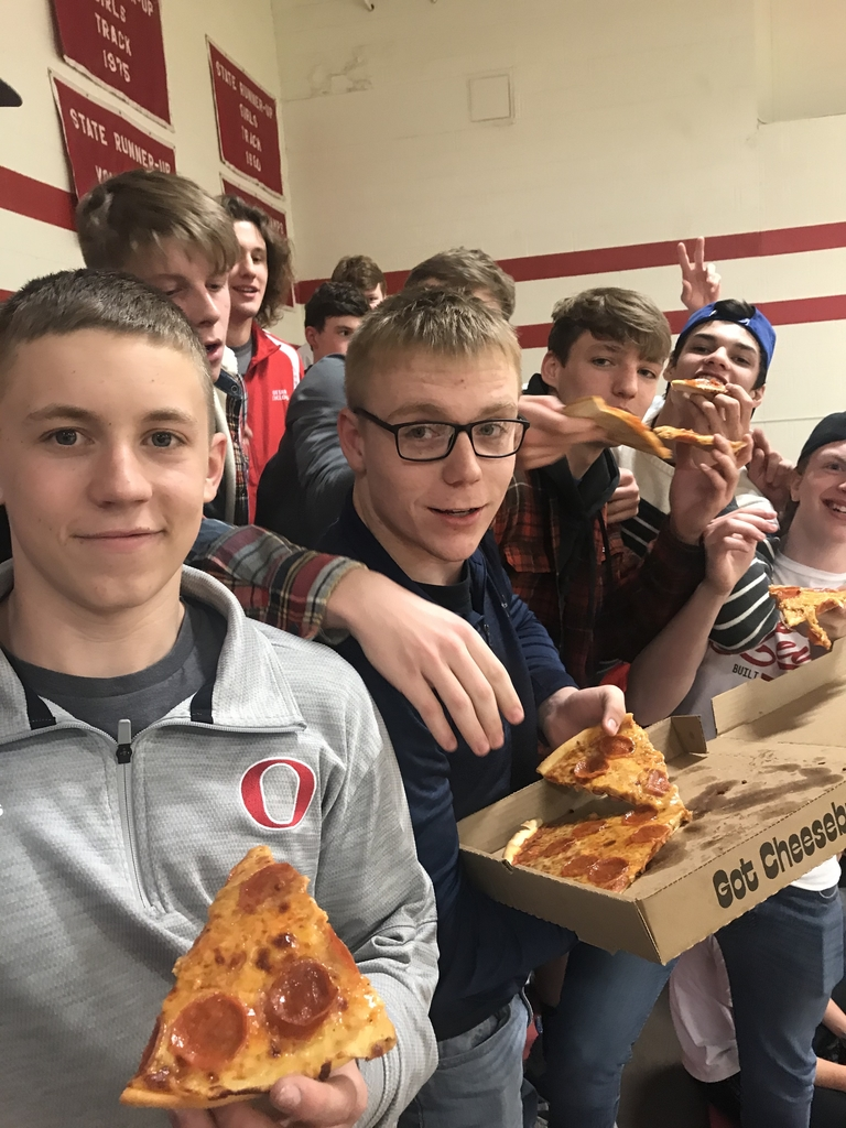 Kids posing with pizza.