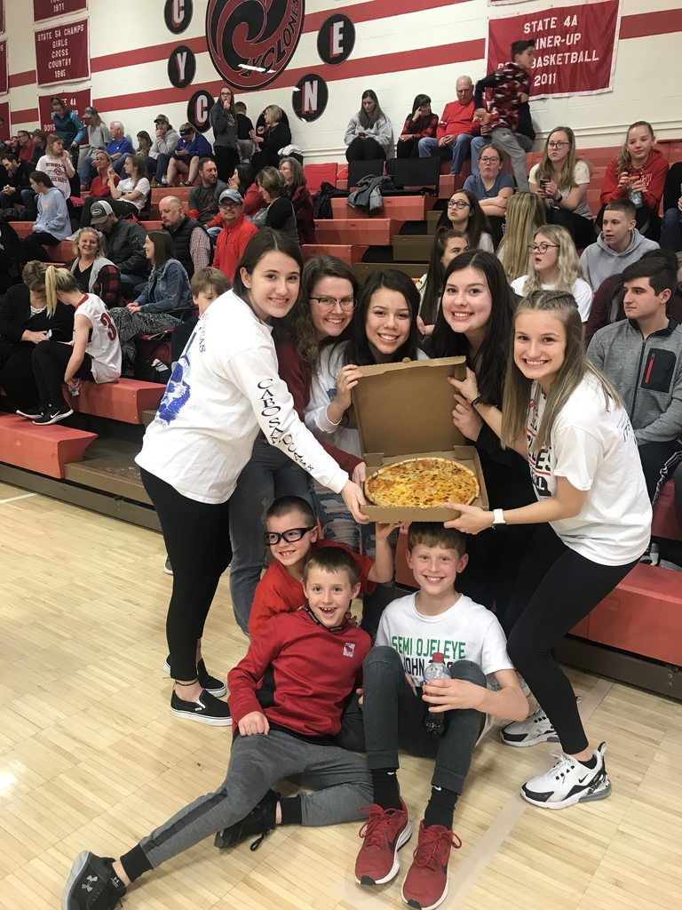 Students posing with a pizza.