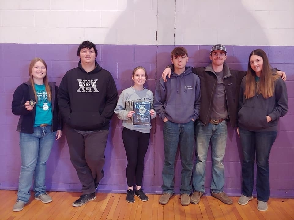 Students posing by a wall with a plaque