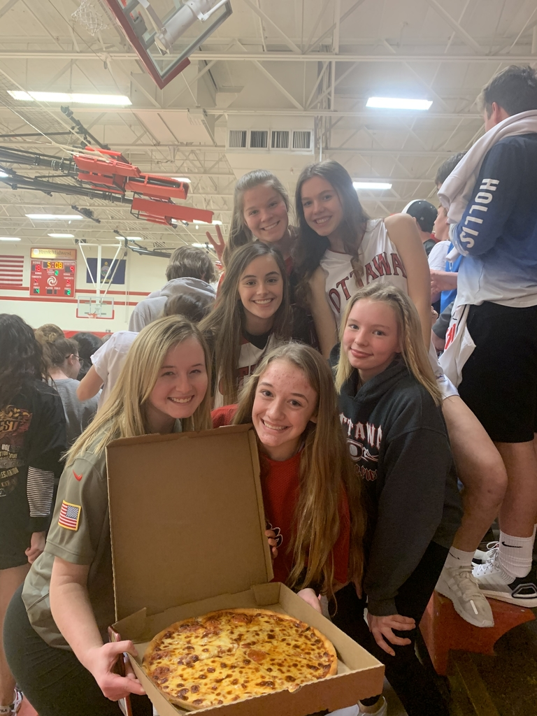 Students posing with a pizza