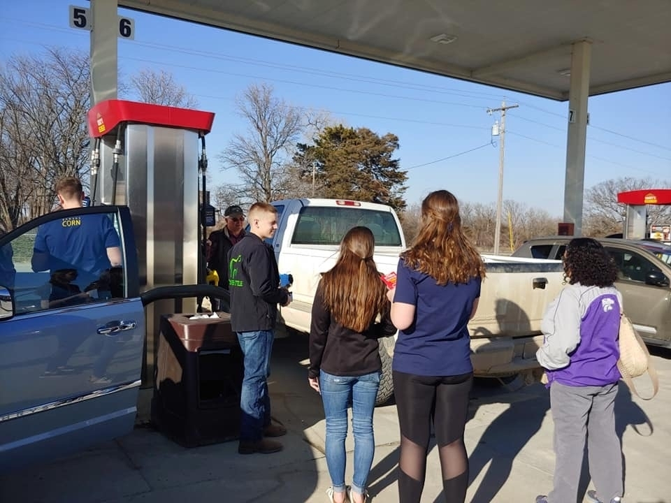 Students at a gas station talking to people.