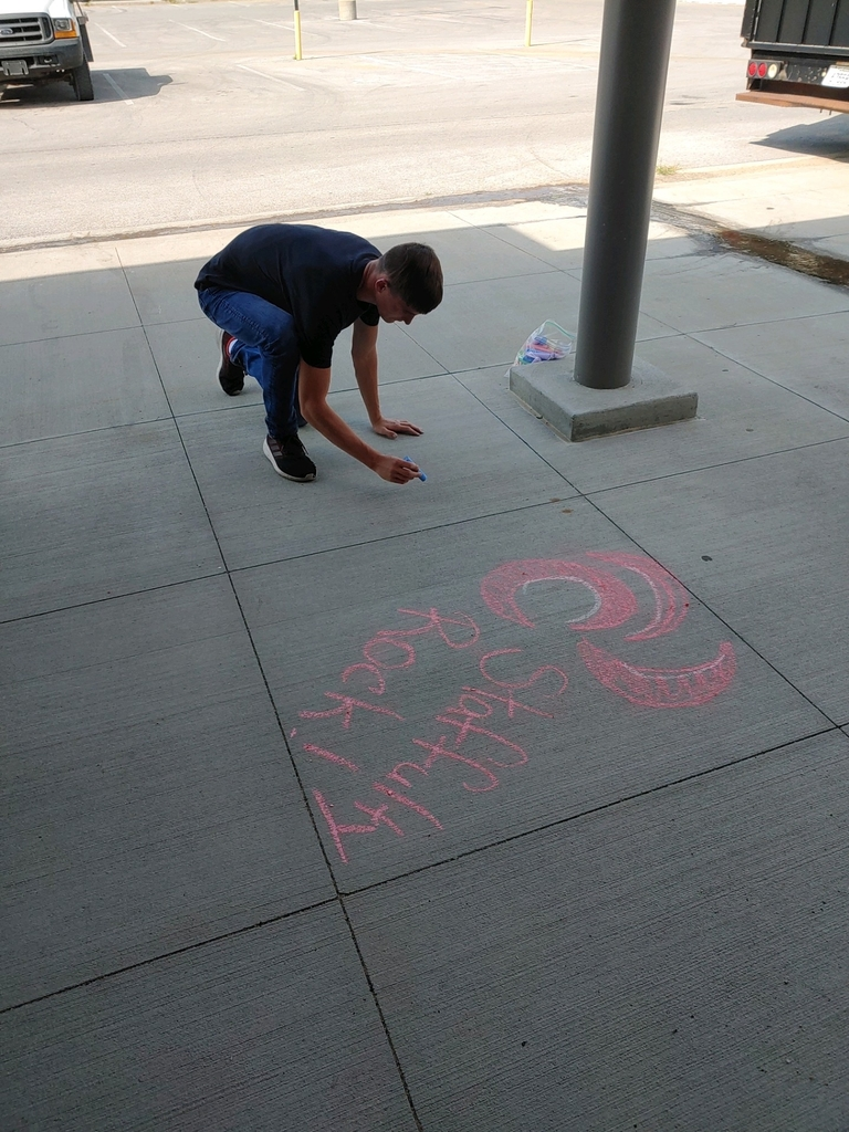 Student writing on sidewalk with chalk