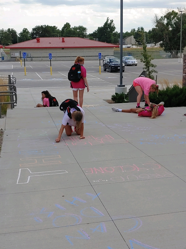 Students writing on the sidewalk with chaulk