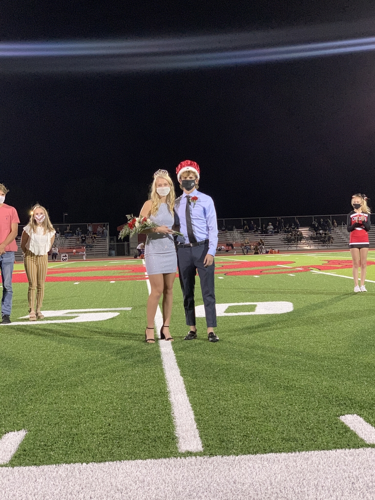 Homecoming King & Queen Standing in a football field.